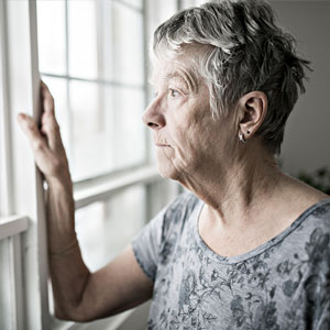 older person staring out a window